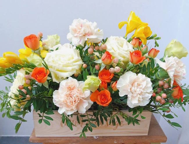 Carnations, orange spray roses and freesias for Mother's Day. Flowers by Cotton and Sage.
