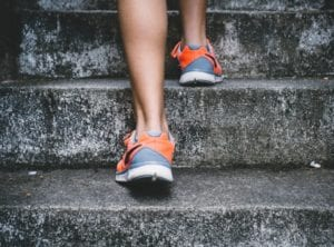 Female feet in trainers running up concrete stairs