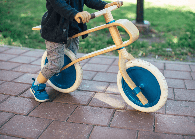 a toddler on a wooden balance bike