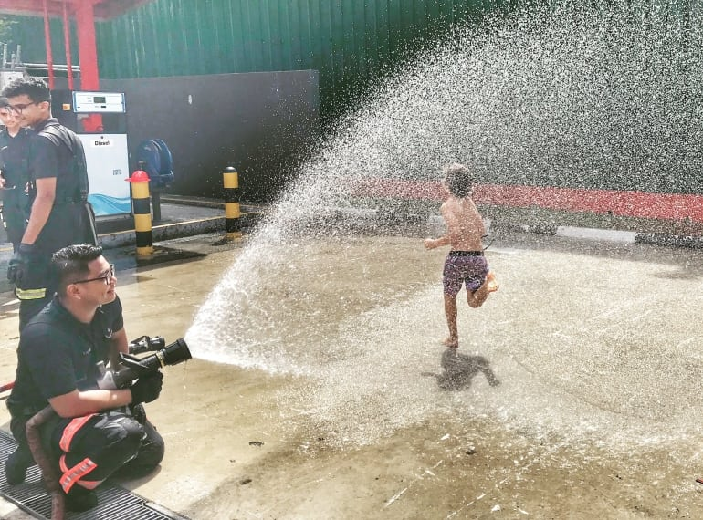 Boy running through water spraying from fire hose