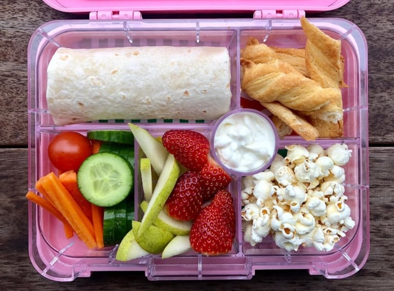 Top view of kids lunchbox, wrap, popcorn, strawberries, cucumber, carrot, tomato - kids lunchbox ideas