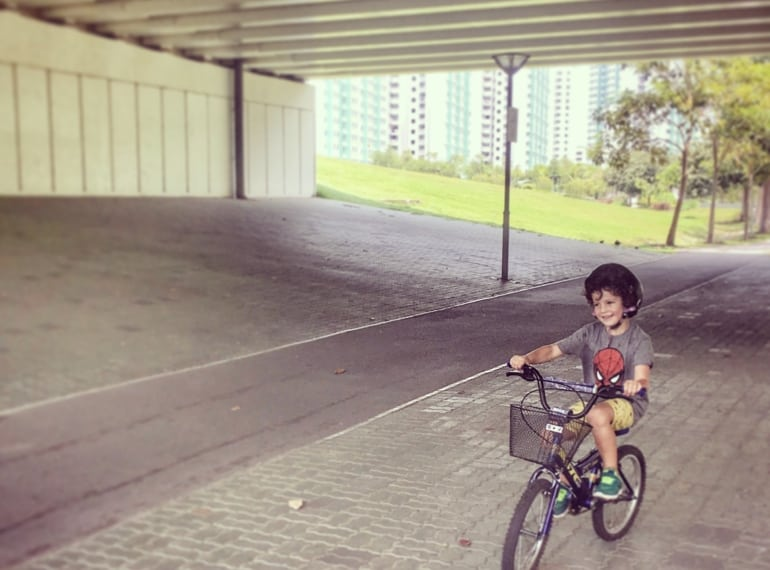 Boy riding his bike at Punggol Waterway Park, green space in Singapore