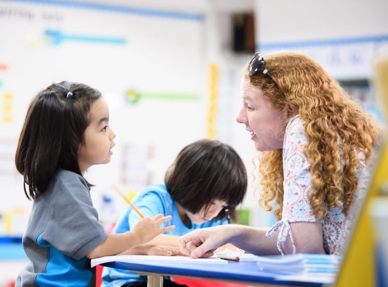 Teacher discussing something with young student at Nexus International School Singapore
