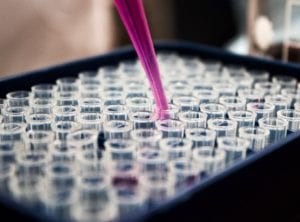 Pink liquid being dropped into test tubes, detecting cervical cancer
