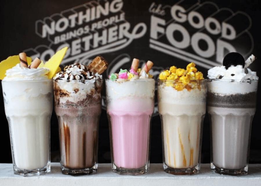 five milkshakes against a black wall