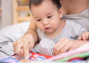 baby reading book with caregiver