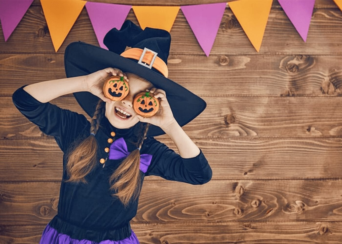 girl in a witch costume holding to jack o'lanterns to her eyes and posing for the camera